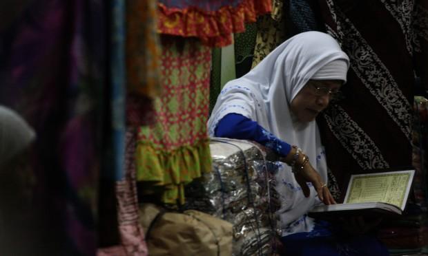 SOLO, 18/8 - MENGAJI. Seorang pedagang membaca Al-Qur'an di Pasar Klewer, Solo, Jateng, Rabu (18/8). Umat muslim meningkatkan berbagai bentuk ibadah seperti membaca Al-Qur'an, melakukan berbagai solat sunah dan kegiatan sosial sebagai salah satu cara untuk meningkatkan kualitas ibadah di bulan puasa Ramadhan. Foto ANTARA/Hasan Sakri Ghozali/10